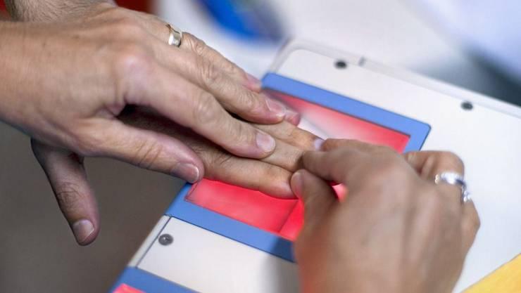 Einem Asylbewerber werden im Empfangs- und Verfahrenszentrums EVZ in Basel Fingerabdrücke genommen.