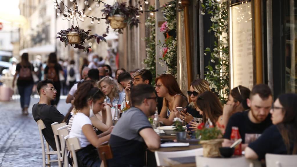 Touristen sitzen im Aussenbereich eines Restaurants in Rom: Schon bald soll das auch wieder in ganz Italien möglich werden. In vielen Regionen des Landes werden die Corona-Regeln entschärft.