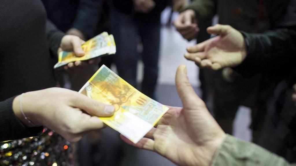 Eine Frau verteilt Zehnernoten mit dem Aufkleber «I love Grundeinkommen» am Hauptbahnhof Zürich.