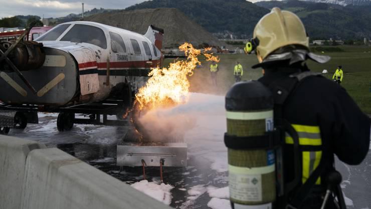 Ein Kleinflugzeug brennt, ein Feuerwehrmann greift ein: Notfallübung auf dem Flugplatz in Thun.