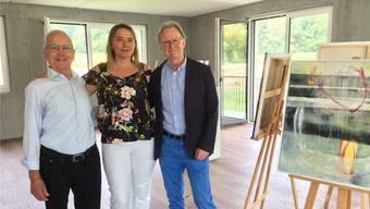 Xaver Lenzin (links), Ursula Steiner-Lenzin und Rolf Imbach im neuen Atelier neben einem Bild der Künstlerin.