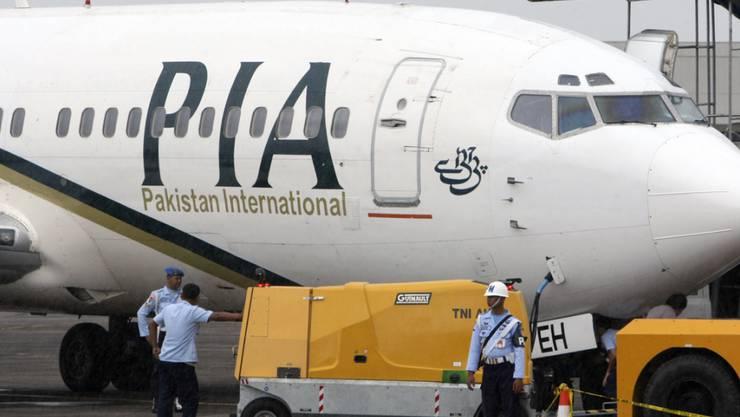 """ARCHIV - Ein Passagierflugzeug der Pakistan International Airlines (PIA) steht auf dem Rollfeld einer Militärbasis. (zu dpa """"Pakistan International Airlines erteilt 150 Piloten Flugverbot"""") Foto: -/AP/dpa"""