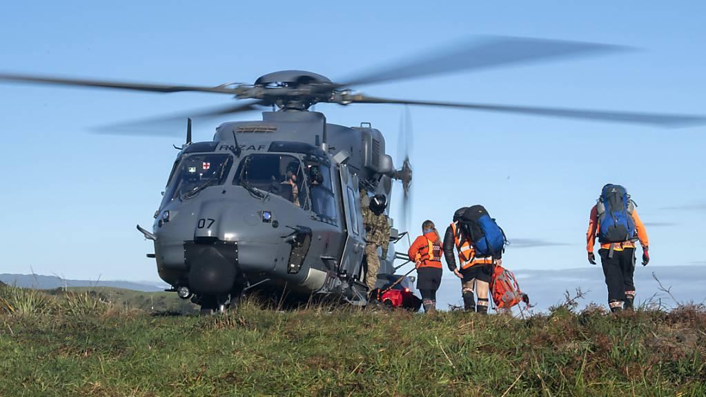 Rettungshelfer gehen während eines Einsatzen an Board eines Hubschraubers. Zwei in der Wildnis Neuseelands vermisste Wanderer sind nach 18 Tagen lebend gefunden worden. Eine Helikopterbesatzung entdeckte am Mittwoch Rauchschwaden eines Feuers, das die beiden 23-jährigen Dion Reynolds und Jessica O'Connor in ihrem selbsterrichteten Notlager im Busch angezündet hatten. Foto: Cpl Naomi James/New Zealand Defence Force/AP/dpa - ACHTUNG: Nur zur redaktionellen Verwendung im Zusammenhang mit der aktuellen Berichterstattung und nur mit vollständiger Nennung des vorstehenden Credits.