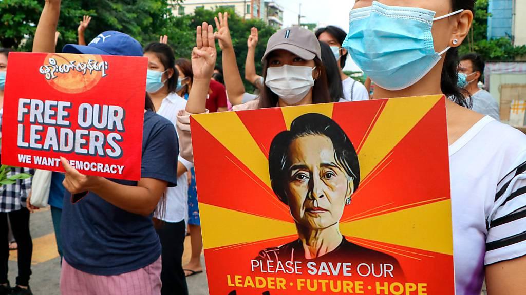 Anti-Putsch-Demonstranten in Yangon halten ein Plakat mit dem Bild der festgesetzten Regierungschefin Aung San Suu Kyi hoch. (Archivbild) Foto: Uncredited/AP/dpa