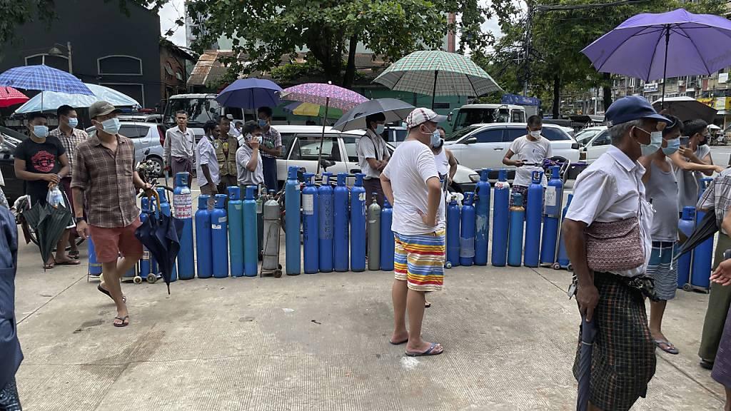 Menschen stehen mit ihren Sauerstoffflaschen vor einer Nachfüllstation in Yangon. Myanmar leidet unter einem Mangel an Sauerstoffkapazitäten, während ein Anstieg der Corona-Fallzahlen zu verzeichnen ist. Foto: Uncredited/AP/dpa