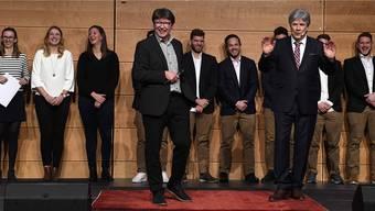 Beat Brunner (v.l.) von Rotweiss Wettingen mit SRF-Moderator Bernhard Schaer (v.r.) vor den Spielern von Rotweiss Wettingen.