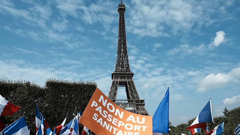 Ein Demonstrant hält während einer Demonstration gegen den Gesundheitspass vor dem Eiffelturm ein Plakat mit der Aufschrift «Nein zum Gesundheitspass» («Non Au Passeport Sanitaire»). Foto: Thibault Camus/AP/dpa