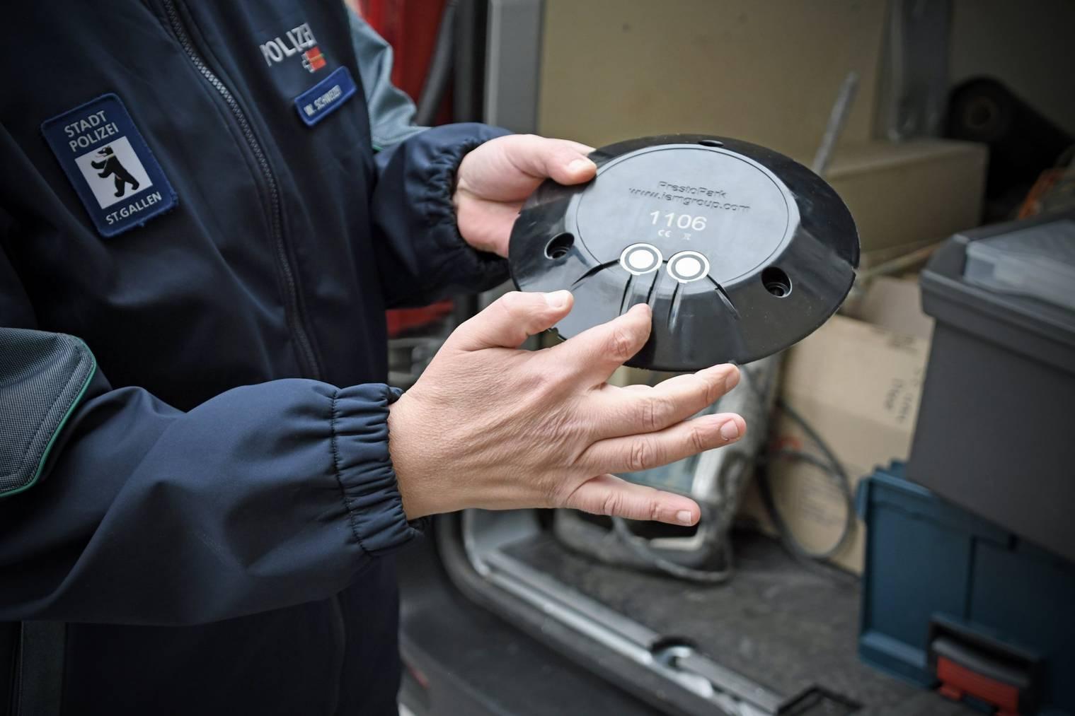 Ein Polizist hält einen Parksensor, wie er beim Pilotprojekt in St.Gallen zum Einsatz kommt.