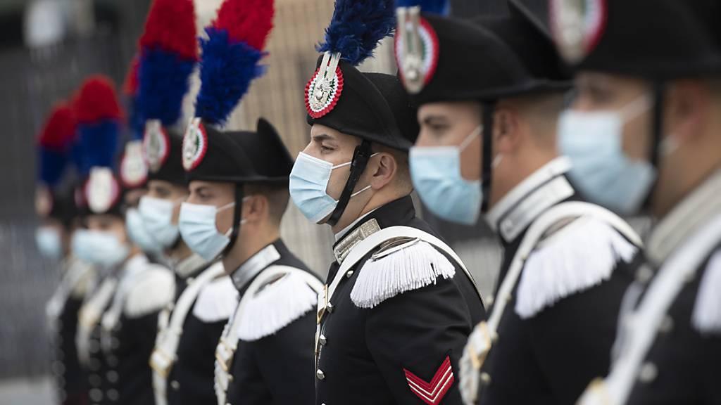 Eine Gruppe italienischer Carabinieri trägt während der Feierlichkeiten zum Tag der Streitkräfte Mund-Nasen-Schutz. Foto: Alessandra Tarantino/AP/dpa