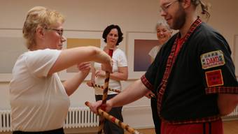 Trainer Fritz-Bodo Kaeding zeigt den drei Frauen, wie sie mit dem Stick richtig schlagen und abwehren.
