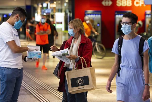 Freiwillige verteilen im Bahnhof Bern Masken.