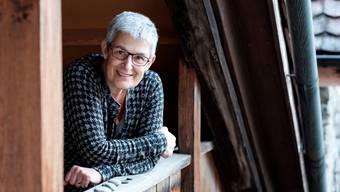 Esther Gebhard auf der Holztreppe ihres Hauses. Die Steine liegen bewusst auf dem Geländer: «Sie geben mir Kraft.»