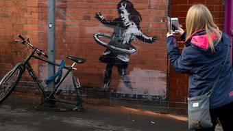 Corona und der Umgang mit der Krise - auch in  den Kunstwerke von Banksy spiegeln sich die Herausforderungen dieses Jahres deutlich wieder: In Nottingham tauchte etwa an einer Hauswand ein Bild eines Mädchen auf, dass mit einem Fahrradreifen Hula-Hoop spielt. Foto: Jacob King/PA Media/dpa - ACHTUNG: Nur zur redaktionellen Verwendung im Zusammenhang mit der aktuellen Berichterstattung.