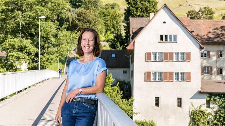 Krimiautorin Ina Haller auf einer Brücke in Brugg, die gemeinsam mit der Mühle im Hintergrund Schauplatz in ihrem Roman «Rüebliland» ist. Vor kurzem ist die Fortsetzung «Chriesimord» erschienen.