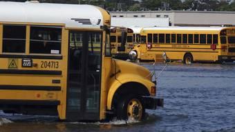 """Ein Schulbus fährt durch das Hochwasser eines überschwemmten Parkplatzes, nachdem Tropensturm """"Eta"""" mit starken Regenfällen über Florida zog. Foto: Joe Cavaretta/South Florida Sun-Sentinel/dpa"""