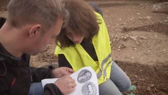 Das Ausgrabungs-Team entdeckt im lehmigen Boden einen Silber-Denar aus der Zeit von Kaiser Augustus.
