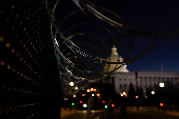 Stacheldraht umrahmt einen Sicherheits-Checkpoint vor dem Kapitol eine Nacht vor Joe Bidens Vereidigung.