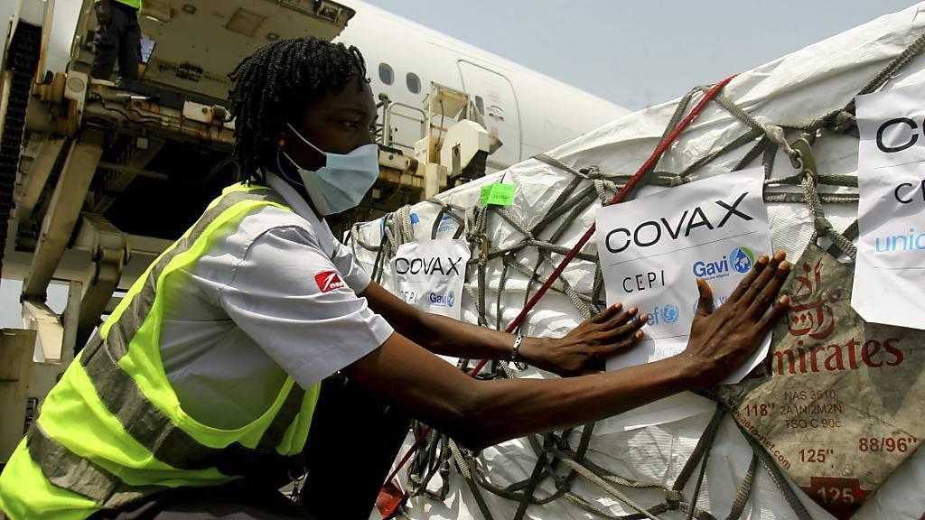 Mit einem Flugzeug gelieferte Dosen des Corona-Impfstoffs von Astrazeneca, hergestellt vom Serum Institute of India, werden am Flughafen in Abidjan in Empfang genommen. Foto: Diomande Ble Blonde/AP/dpa