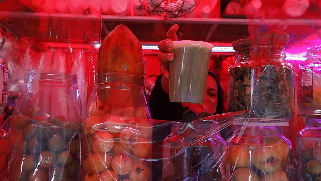 Eine Verkäuferin serviert einen grünen Saft in einem Einweg-Plastikbecher an einem Strassenstand im Zentrum von Mexiko-Stadt.