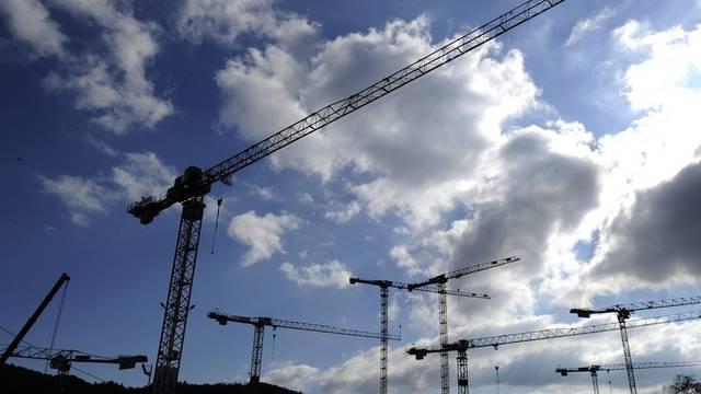 Baukräne ragen auf einer Baustelle in den Himmel (Archiv)