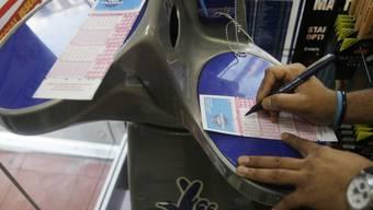 Ein Mann füllt einen Lotterieschein in London aus (Symbolbild)