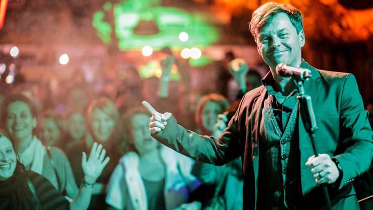Florian Ast posiert mit dem Publikum im Rücken.