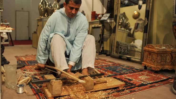 Ein Hanwerker drechselt mit Händen und Füssen Schachfiguren und Honiglöffel.