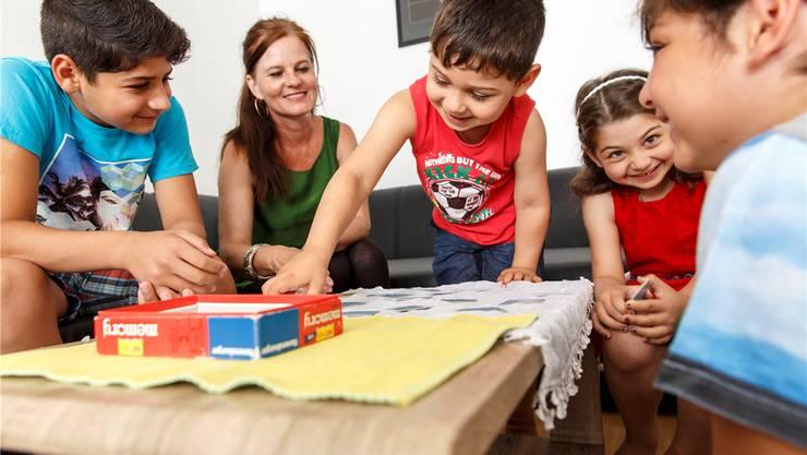 Heilpädagogin Franziska Affolter spielt mit den Kindern der Familie Hazzore aus Syrien Memory.