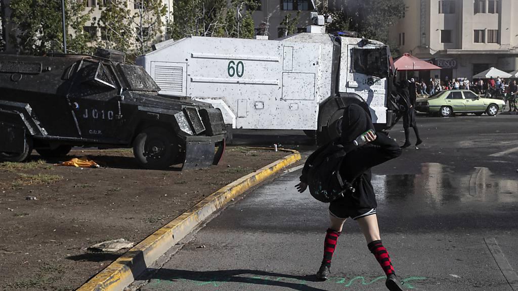 Eine Demonstrantin wirft eine Flasche auf einen Wasserwerfer der Polizei während einer Demonstration in Santiago de Chile am Internationalen Frauentag. Foto: Esteban Felix/AP/dpa
