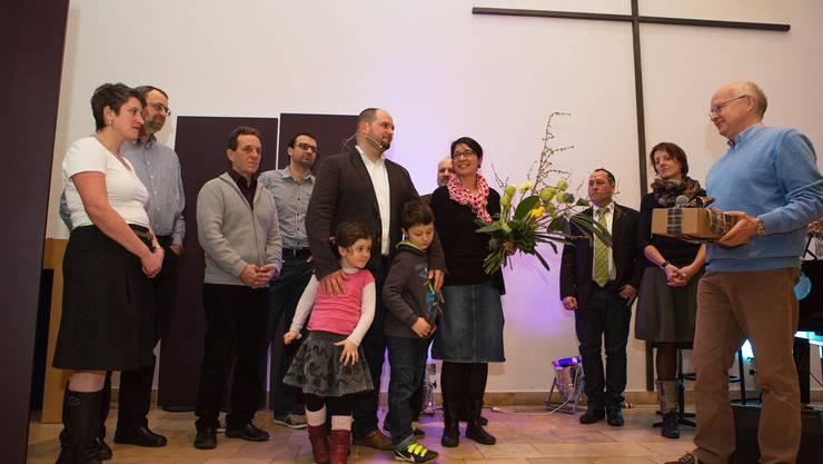 Martial Sollberger mit Ehepartnerin und Kindern (Bildmitte) begrüsst durch Kirchgemeinde-Präsident Geri Heiniger (r.) zusammen mit Gesamt-Vorstand und Angestellten.