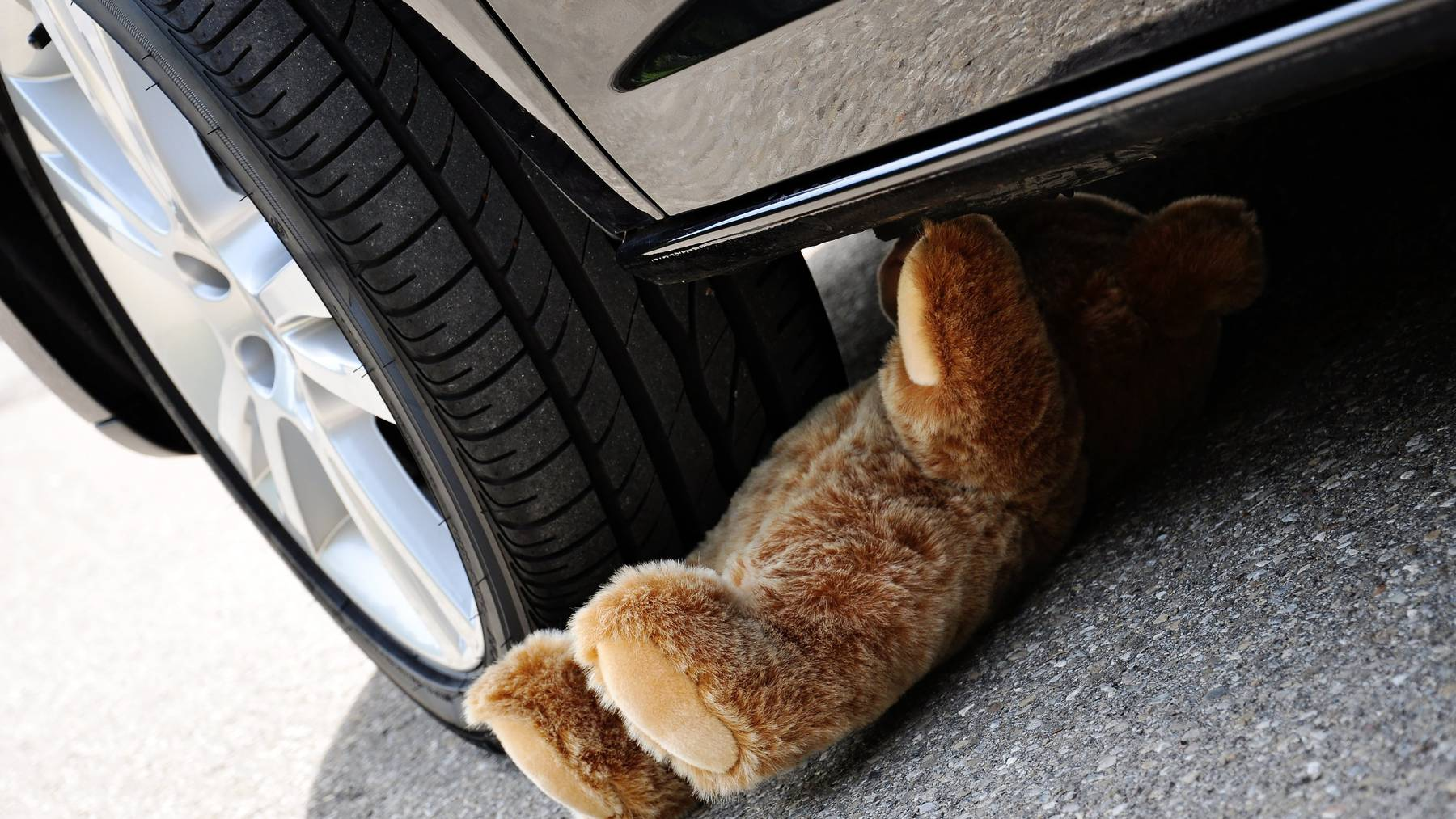 Teddy under car tires, symbolic car accident with playing children