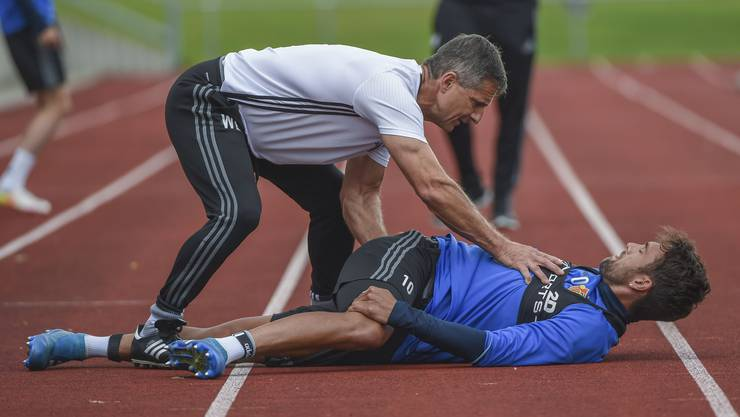 So wirds gemacht: Werner Leuthard, Leiter Fitness beim FC Basel, zeigt Captain Matias Delgado, wie er sich dehnen muss.