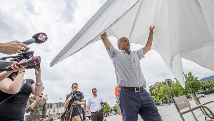 FDP-Stadtrat Filippo Leutenegger öffnet einen von rund 20 Sonnenschirmen, die vorerst zwischen August und September getestet werden.