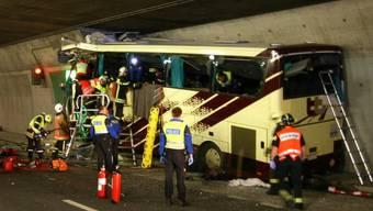 Rettungskräfte untersuchen das Wrack des verunglückten Cars im Tunnel in Siders