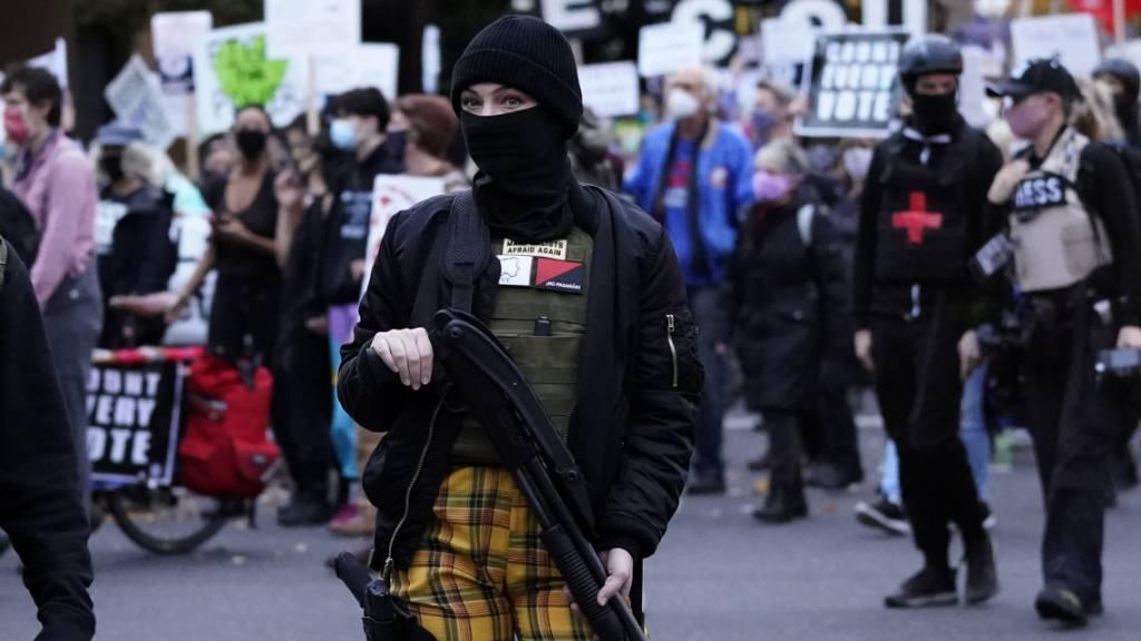 dpatopbilder - Eine Frau trägt während einer Demonstration in Portland für die Auszählung aller Stimmen im Rahmen der Präsidentschaftswahl eine Waffe. Foto: Marcio Jose Sanchez/AP/dpa