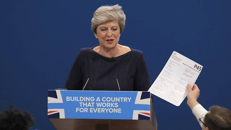 Der Komiker Simon Brodkin hält Regierungschefin Theresa May während ihrer Rede das Entlassungsformular P45 hin