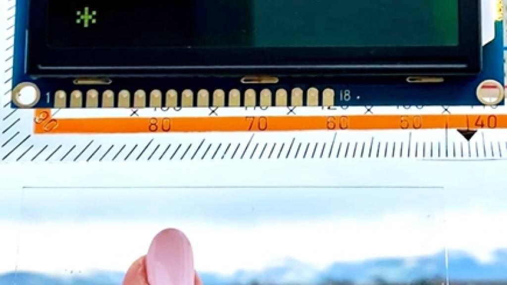 Nur Eingeweihte wissen, dass der Zugangscode auf der Folie am Fensterglas eingegeben werden muss: Forschende bedruckten eine Klarsichtfolie mit einer speziellen Tinte, um ein unsichtbares Türschloss zu entwickeln. (Pressebild)