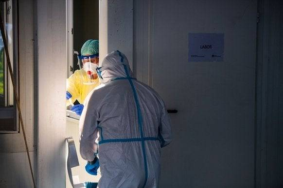Ein Mitarbeiter des Testzentrums Garmisch-Partenkirchen übergibt ein Teströhrchen zu einer Mitarbeiterin im Laborcontainer.