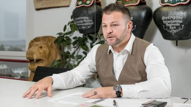 Markus Birchmeier sitzt im «Glockenzimmer» am Hauptsitz der Birchmeier Gruppe in Döttingen, wo seine Schwingtrophäen an der Wand hängen.
