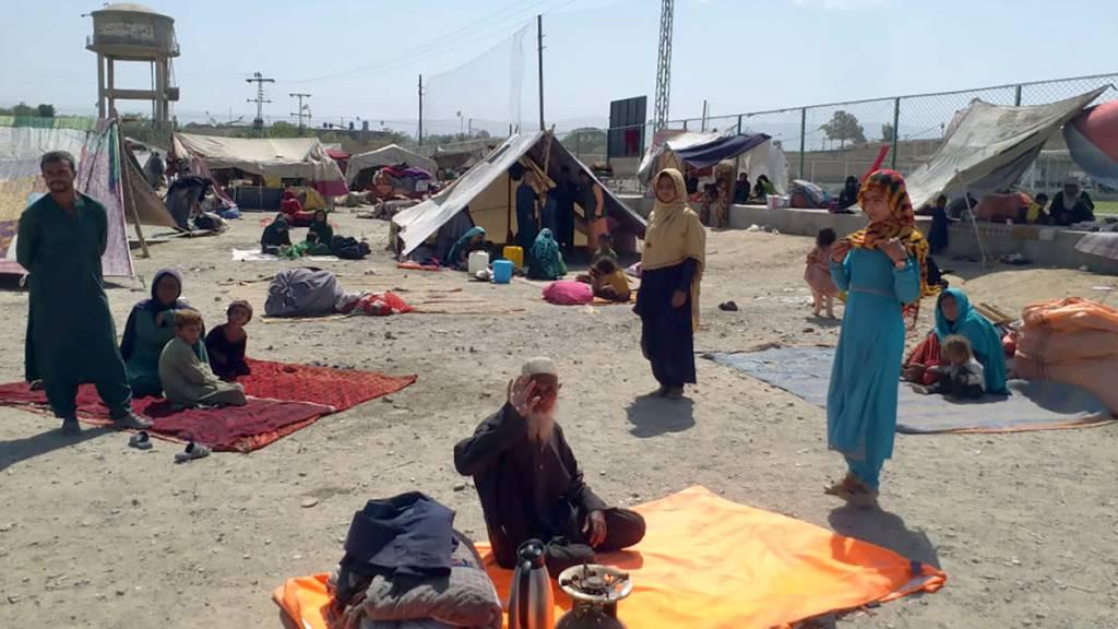 Afghanische Familien sitzen vor ihren Zelten am Rande von Chaman, einer Grenzstadt in der südwestlichen pakistanischen Provinz Belutschistan. Foto: Jafar Khan/AP/dpa