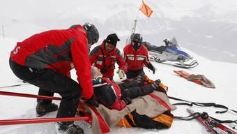 Eine Pistenpatrouille kümmert sich um einen verunfallten Skifahrer