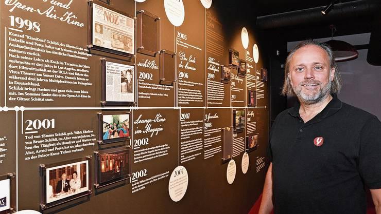 Kino Koni Konrad Schibli vor der Museumswand, auf welcher die Entwicklung der Oltner Kinoszene festgehalten ist.