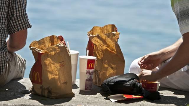 Zwei Männer mit McDonald's-Produkten (Archiv)