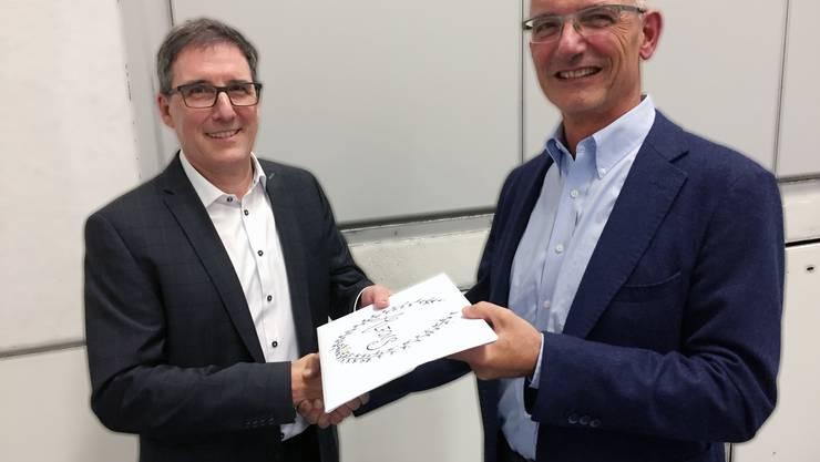 Der neue Golfclub-Präsident Dr. Lukas Eisner (rechts) übergibt seinem Vorgänger Alfons Hürzeler ein Abschiedsgeschenk. Foto Markus Emch, agentur meo verlag ag