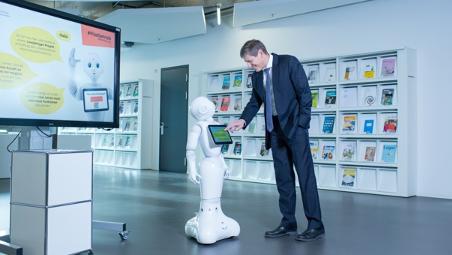 Daniel Halter, Vizepräsident Hochschulentwicklung FHNW, mit Roboter Pepper in der Bibliothek des Campus Brugg-Windisch.