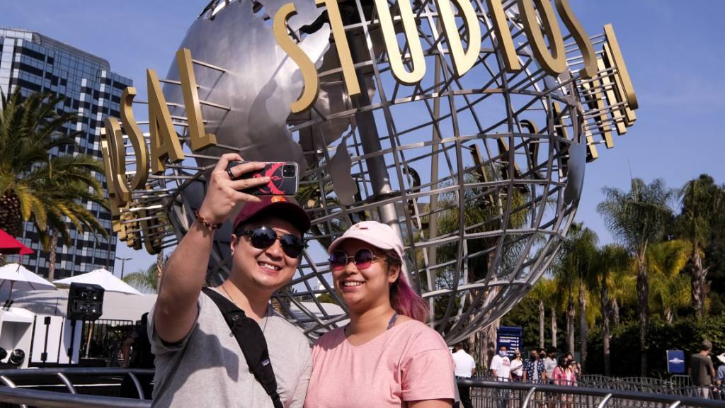 Ein Paar fotografiert sich vor dem Schriftzug Universal Studios Hollywood auf einer Weltkugel-Skulptur. Am Dienstag hob Kalifornien die meisten seiner COVID-19-Beschränkungen auf und läutete das ein, was als die «Große Wiedereröffnung» des Staates bezeichnet wurde. Foto: Ringo H.W. Chiu/FR170512 AP/dpa