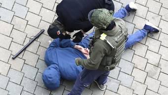 Polizisten nehmen während eines Protests der Opposition in Minsk einen am Boden liegenden Mann fest. Foto: ---/AP/dpa