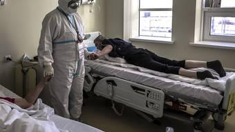 dpatopbilder - Der Bischof (M) der Russisch-Orthodoxen Kirche, Panteleimon, tröstet Patienten, die im Verdacht stehen, das Coronavirus zu haben, in einem Krankenhaus in Kommunarka, außerhalb von Moskau. Foto: Sophia Sandurskaya/Moscow News Agency/dpa
