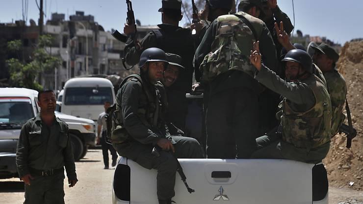 Syrische Polizei-Einheit mit Siegeszeichen in den Strassen von Duma