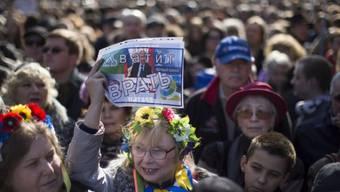 """""""Hört auf zu lügen"""" steht auf dem Plakat der Demonstrantin"""